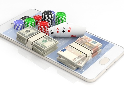 a mobile phone with casino chips, cards, and cash sitting on it